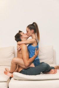 44408277 - young guys kissing on the couch, home free